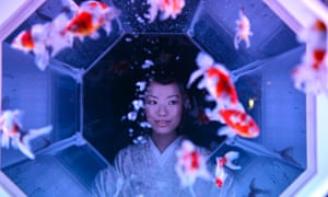 A young woman looks at goldfish swimming in a fish tank during the preview of the 'Art Aquarium 2013' exhibition at Nihonbashi Mitsui Hall in Tokyo, Japan. 5,000 goldfish are on display at the exhibition.