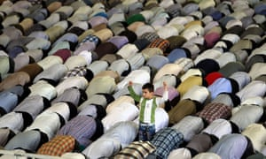 A young boy stands among worshippers attending Friday prayers during the Muslim fasting month of Ramadan in Tehran, Iran