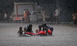 People help a family pick up their motorcycle after it slipped on a flooded road during monsoon rains in Mumbai.