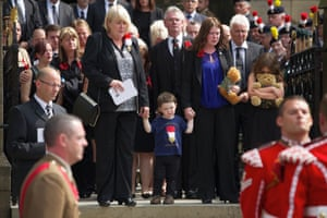 Fusilier Lee Rigby's son Jack, flanked by his mother Rebecca and Lee's mother Lyn, watch his coffin leave following his funeral at Bury Parish Church.