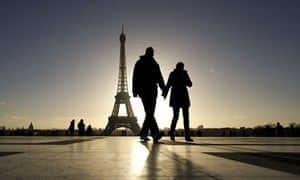 Tourists walk by the Effel Tower