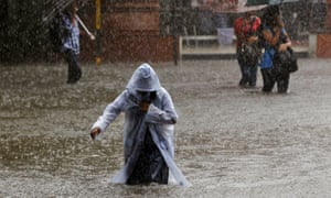 An Indian girl wearing a raincoat wades through a flooded street as it rains in Mumbai, India as heavy rains lashed the city.