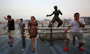 Everybody was kung fu fighting. Tourists pose in front of a bronze statue of the late kung fu legend Bruce Lee on the waterfront facing Hong Kong. 20 July marks the 40th anniversary of the death of Lee, with a memorial event and exhibition to be held by his fan club and the government.