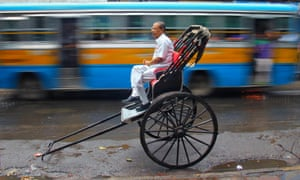 Going nowhere fast. A commuter waits for a rickshaw puller along a busy road in Kolkata, India.