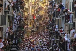 20 Photos: People on balconies look at bull run of the San Fermin Festival
