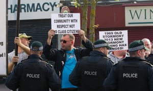 Nationalist protesters at the Ardoyne shopfronts as Orange marchers go by.