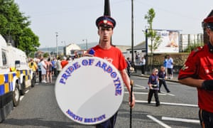 A bandsman holds up a spare skin for a bass drum with his band's name, Pride of Ardoyne.