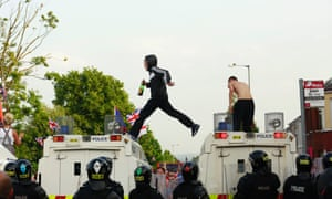 Loyalists climb onto police vehicles during a clash with police in the Woodvale Road area of North Belfast.