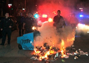 Zimmerman not guilty: Police officers work to extinguish a fire during a protest in Oakland
