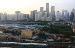 A China Railway High-speed (CRH) Harmony bullet train (bottom) drives past Beijing's central business district, July 11, 2013.