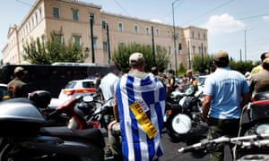 """A striking Municipal police officer draped with a Greek flag and bearing a sign reading """"Not for sale"""" during a protest, against new austerity cuts that will affect thousands of public sector workers, outside the Greek Parliament in Athens, Monday, July 15, 2013."""