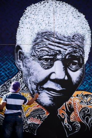 South African artist John Adams works on a giant acrylic-on-canvas painting of Nelson Mandela in the driveway of his house in a suburb of Johannesburg, South Africa. Adams said he felt driven to create the painting as thanks to Mandela for creating educational opportunities that enabled him to become an artist.