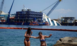 Sunbathers walk on rocks as the Costa Concordia cruiser is visible in background on the Isola del Giglio, Italy. Salvage crews are working against time to right and remove the shipwrecked Costa Concordia cruise ship, which is steadily compressing down on itself from sheer weight onto its granite seabed.
