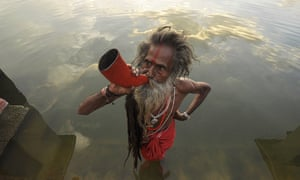 An Indian sadhu blows a buffalo horn on the eve of the traditional Kharchi Puja festival at Agartala, India.  Kharchi Puja is one of the most important festivals of Tripura and is a week-long festival during which fourteen gods are worshipped.