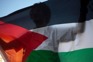 A protester holds a Palestinian flag during a demonstration against an Israel's plan to relocate nearly thirty thousand Bedouins from the southern Negev desert, in Tel Aviv, Israel. Hundreds of protesters have staged demonstrations against a plan to resettle nomadic Bedouin Arabs in the southern Negev desert. Bedouins claim that the plan would confiscate their land and destroy their way of life. Photograph: Ariel Schalit/AP