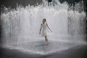 A girl stands surrounded by the jets of a fountain on the South Bank on a hot summer day in central London, England. Photograph: Andrew Winning/Reuters