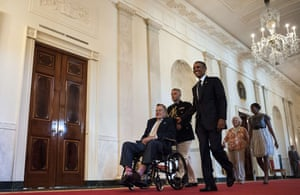 US President Barack Obama (C) walks with former President George H. W. Bush (L) as Barbara Bush (2R) and US first lady Michelle Obama (R) follow to an event in the East Room of the White House in Washington, DC. Obama hosted former US President George H. W. Bush and Barbara Bush to honor the 5000th Daily Point of Light Award which is a program started in response to Bush's call for volunteerism.