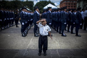 A four years old child dressed as a police salutes next to members of the Academy of National Civil Police of Guatemala during the commemoration of the 16th anniversary of the institution in Guatemala City. The National Civil Police was created in 1996 in the frame of the peace agreements to replace the National Police, which was accused over serious violations on human rights during the 36 years armed conflict in the country. Photograph: Saul Martinez/EPA