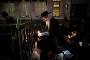 An Ultra Orthodox Jew holds candle and prays as he reads from the book of Eicha (book of Lamentations) during Tisha B'av at the Yeshiva in Mea Shearim neighborhood in Jerusalem. Religious Jews stay up all night and sleep at the Western Wall as they recite lamentations focusing on the destruction of the ancient temple, that was located on the other side of the ancient wall, on the Temple Mount. Photograph: Abir Sultan/EPA