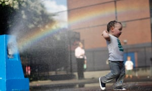 A young boy cools off in the water from a playground sprinkler in the Brooklyn borough of New York. Temperatures are set to top out in the mid-90s degrees Fahrenheit (35 degrees Celsius) through Thursday in New York City, Philadelphia and Washington, D.C. Photograph: Brendan Mcdermid/Reuters