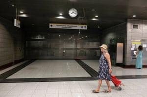A commuter walks by a closed train station in a northern Athens suburb July 16, 2013