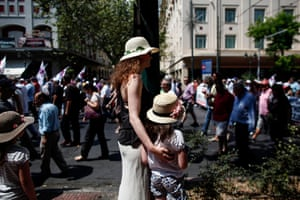 Tourists watch as union members stage a demonstration against the Greek government during a general strike in Athens on July 16, 2013
