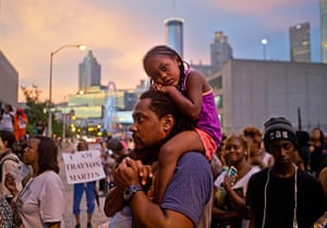 Trayvon protests: Atlanta: A girl sits on her father's shoulders during a protest over George
