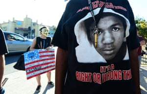 Trayvon protests: Los Angeles: A man wears a single bullet around his neck over his Trayvon t