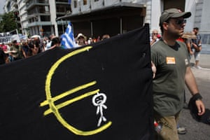 A protester holds a banner featuring a man hanging from a Euro logo as he marches to the Greek Parliament during a protest in Athens, Tuesday, July 16, 2013.
