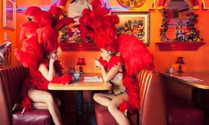 Two showgirls drinking cocktails in bar