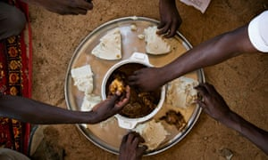 Men share a midday meal at Kerfi in eastern Chad