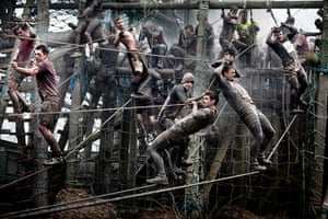 Tough Guy - Weekend: Men climb along ropes in muddy conditions