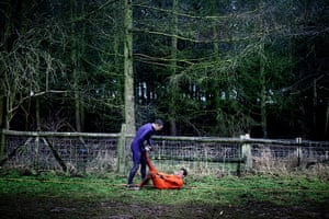 Tough Guy - Weekend: Man in blue helping another man in red with cramp in forest
