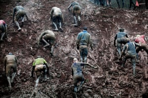 Tough Guy - Weekend: Men climb up a muddy hill at the annual Tough Guy competition