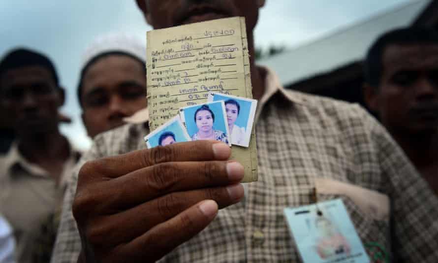 Rohingya asylum-seeker Mohammad Zuhar bin Sayed Alam displays pictures of his wife Nuranki and sister Rajuma he left behind in Myanmar.