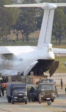 Thai security forces unload a plane from North Korea that landed in Bangkok carrying missiles