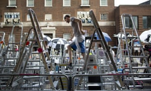 A press photographer climbs across the forest of stepladders to check his position outside the Lindo Wing of Saint Mary's Hospital in London where the royal baby is expected to be born some time soon.