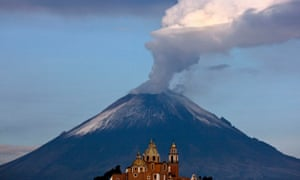 Towering over San Pedro Cholula town in Puebla, Mexico a column of steam and ash rises from Popocatepetl volcano.