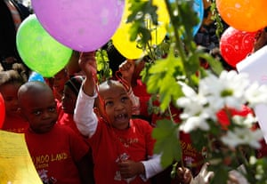 Mandela's birthday: Children hold balloons and flowers as they gather outside the hospital in P