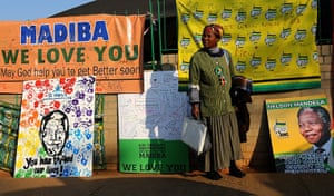 Mandela's birthday: A woman stands in front of posters and get well messages outside the Medi-C