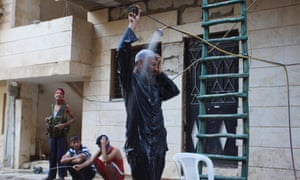A Free Syrian Army fighter takes a shower in his clothes and calls on others to do the same to avoid being surprised by enemies in Deir al-Zor.