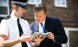 Um, no, they're not browsing Facebook...PC Kris Seward is showing David Cameron a new PC based mobile device during a visit to look at new community police crime prevention initiatives in Cheshunt.