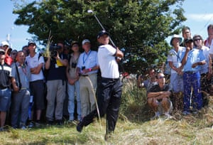Tiger Woods swings his way out of the rough on the first hole at sunny Muirfield in Scotland.