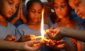 School children light candles as they pay tribute to the victims of the food poisoning.