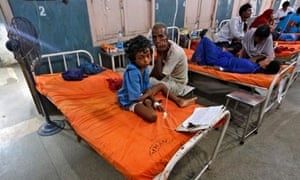A sick girl sits next to her grandfather after she ate contaminated meals at school in Patna, India