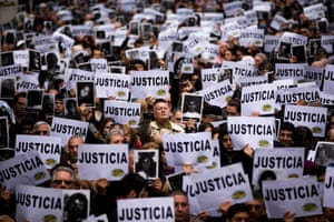 """People hold up signs that read in Spanish """"Justice,"""" and pictures of the victims of the bombing of the AMIA Jewish community center, on the 19th anniversary of the terrorist attack in Buenos Aires, Argentina. The bombing of the Argentine-Israeli Mutual Association in downtown Buenos Aires killed 85 people in 1994 and remains unsolved."""