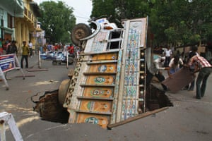 Mind the gap - labourers try to salvage the contents of a truck, trapped after a road caved in, Ajmer, India.