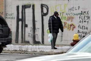 motor city blues: A pedestrian walks by graffiti in downtown Detroit