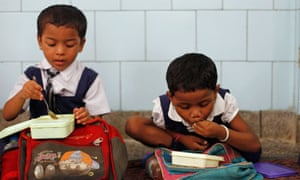 Indian schoolgirls eat their free midday meal in New Delhi