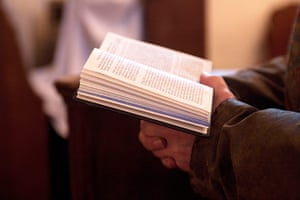 CofE: A member of the congregation follows the service